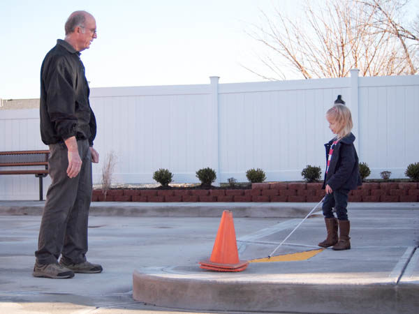 Certified Orientation and Mobility Specialist instructing young child how to navigate their environment.