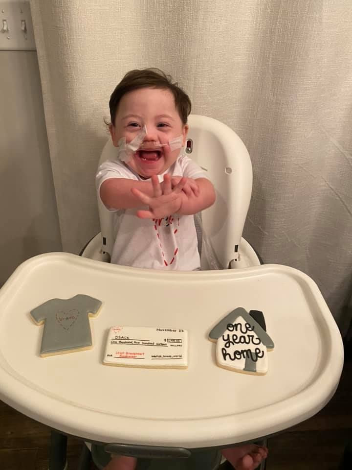 Little Wally sits at his high chair, smiling happily, with cookies displayed in front of him celebrating his year anniversary of being home from the hospital.