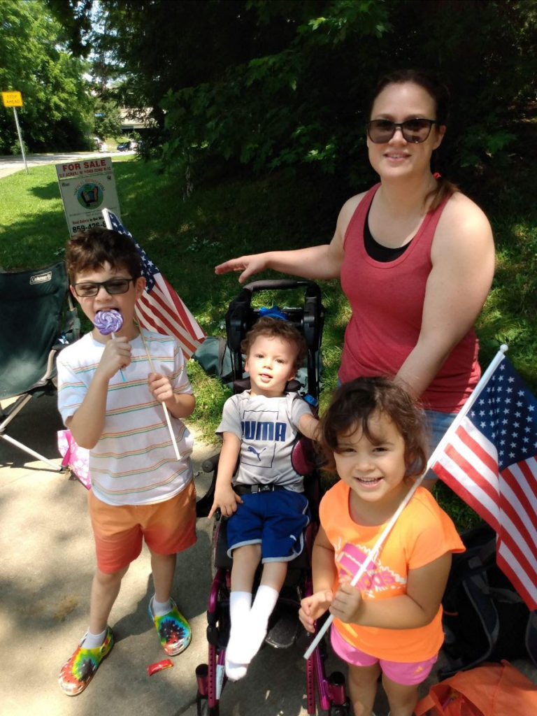 Isaac sits in his stroller with mom, Traci, next to him, and siblings, Haddon and Noel smiling nearby.